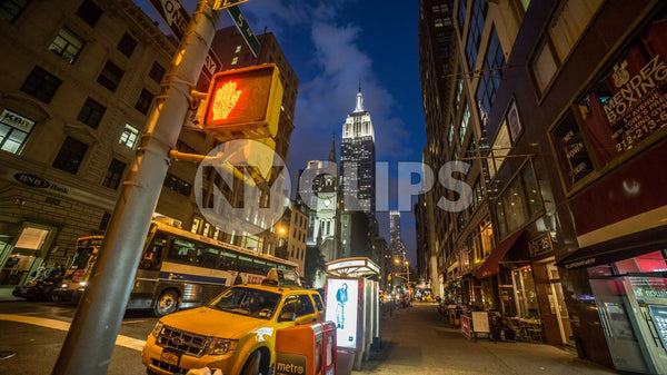 Empire State Building at night on 5th Avenue with taxicab parked on corner in Manhattan