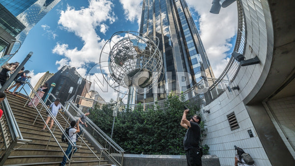 Columbus Circle with tourist photographer taking photo - famous globe sculpture and Trump Tower and people in Midtown Manhattan on sunny summer day from subway station stairs in NYC