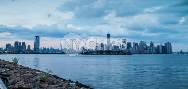 Downtown Manhattan skyline with skyscrapers and East River water view from Brooklyn with rocks in foreground in early evening