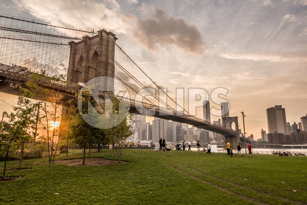 Brooklyn Bridge Park with people enjoying sunset with Manhattan skyline across East River in NYC summer