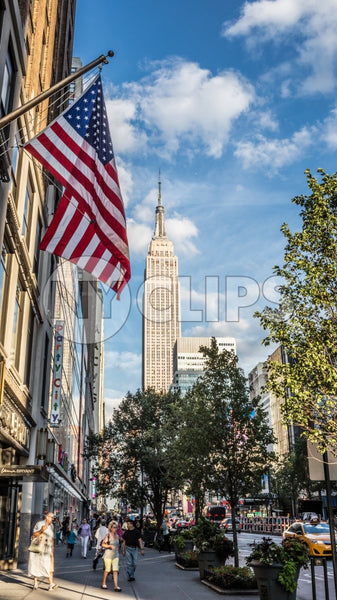 Empire State Building and American flag - summer day in Manhattan - street view of tall landmark skyscraper