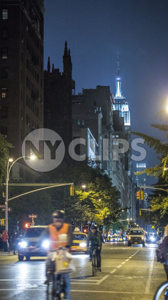 Empire State Building at night from Lower 5th Ave with bicycle delivery boy riding bike with helmet