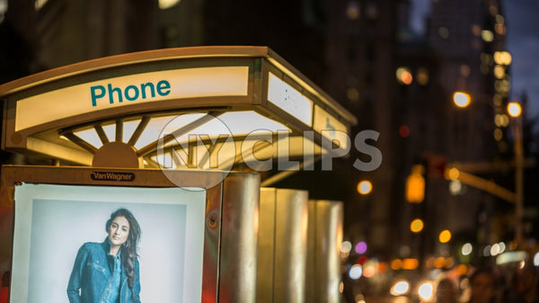 public pay phone with ad of beautiful model at night in Manhattan