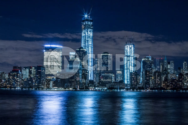 Downtown Manhattan skyline with Freedom Tower and skyscrapers at night reflections off East River water