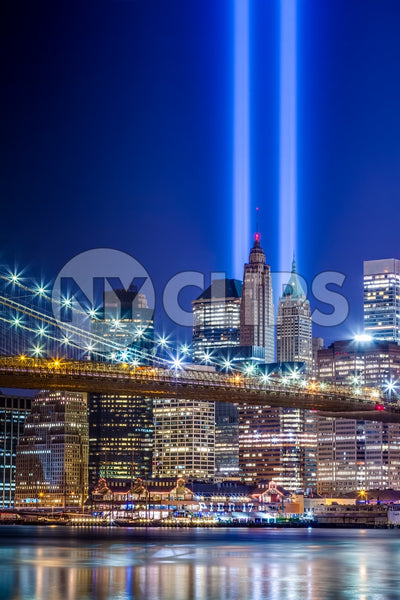 September 11th beams over skyscrapers in Manhattan from across East River water at night