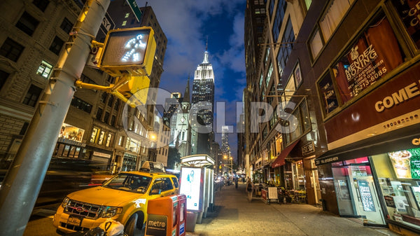 Lower 5th Ave at night with Empire State Building and walk light and parked caravan taxi cab