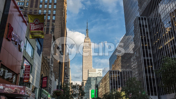 Empire State Building view from 34th Street and the west side of Manhattan on summer day with bright blue sky