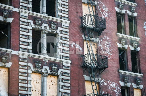 abandoned tenement with fire escapes - boarded up windows - gritty graffiti on red building in ghetto