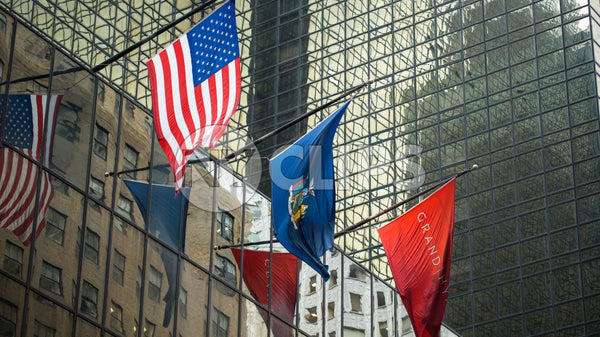 3 flags on corporate office building - American flag in Midtown Manhattan during day
