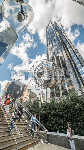 upward angle of Columbus Circle with famous globe sculpture and people in Midtown Manhattan on sunny summer day from subway station stairs in NYC