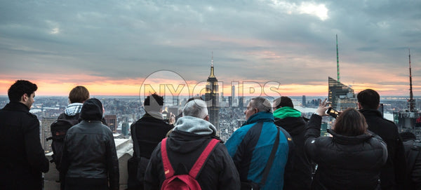 tourists taking photo of Empire State Building in Manhattan observation deck at sunset NYC