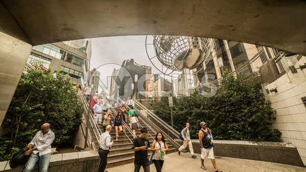 Columbus Circle with famous globe sculpture and student with backpack in Midtown Manhattan on sunny summer day from subway station stairs in NYC