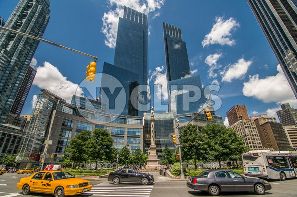Time Warner Towers at Columbus Circle during day, blue sky in summer with cars and taxi cab driving around circular street