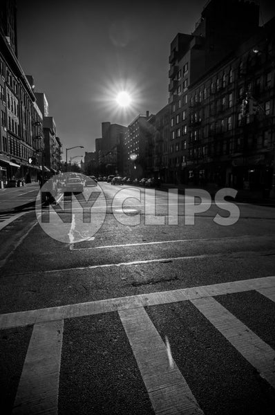 sunny day in Harlem - black and white crosswalk and bright sun shining on street