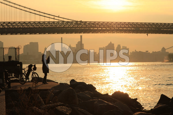 woman taking picture of Manhattan Bridge at sunset - beautiful orange sky over East River from Brooklyn