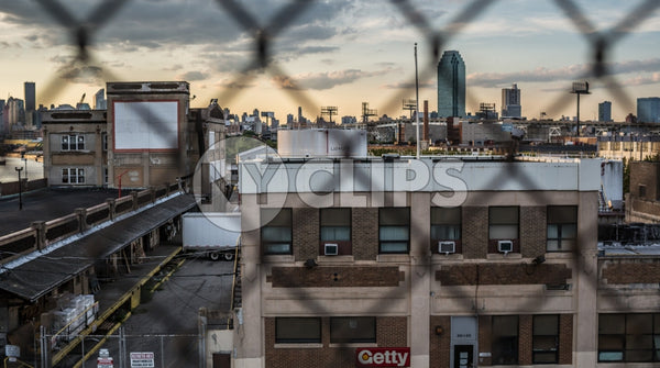 gritty view of Brooklyn through fence at sunset with Manhattan buildings and skyscrapers in background in NYC