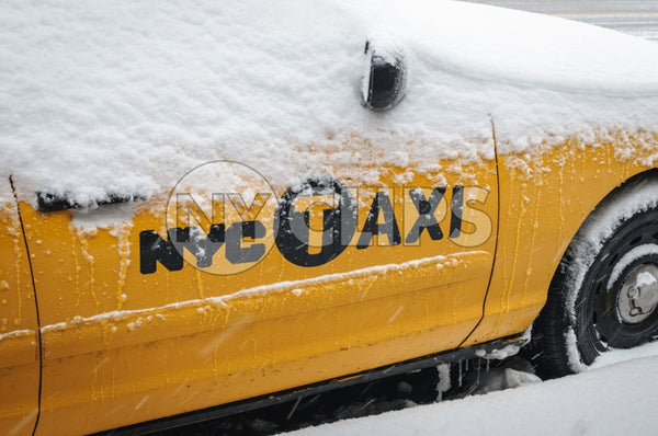 taxicab covered in snow - snowing in winter blizzard