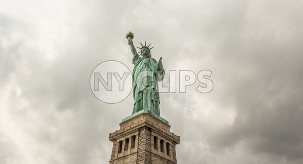 Statue of Liberty on cloudy day - far shot with full body and base