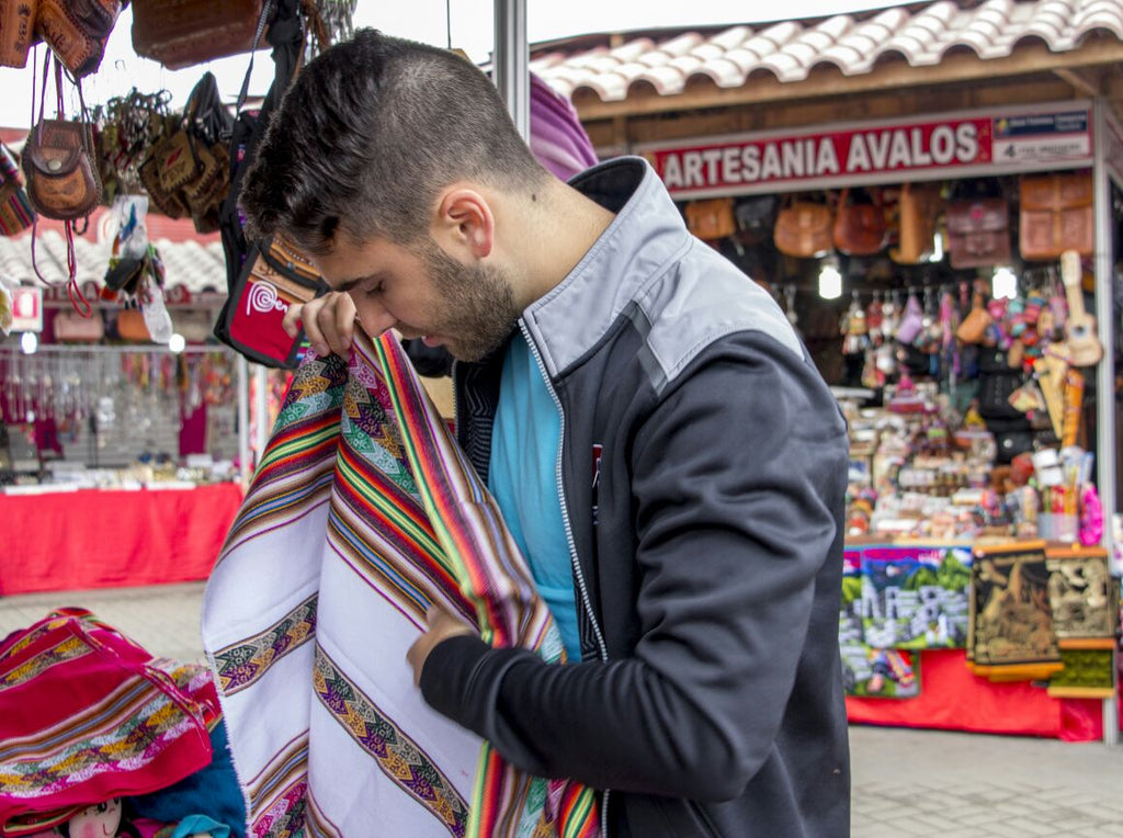 PATOS Shoes Founder Fernando Rojo picking out patterns at a local artisan fair.