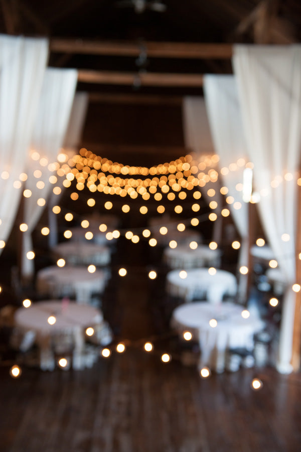 barn wedding reception with bistro lights and drapes
