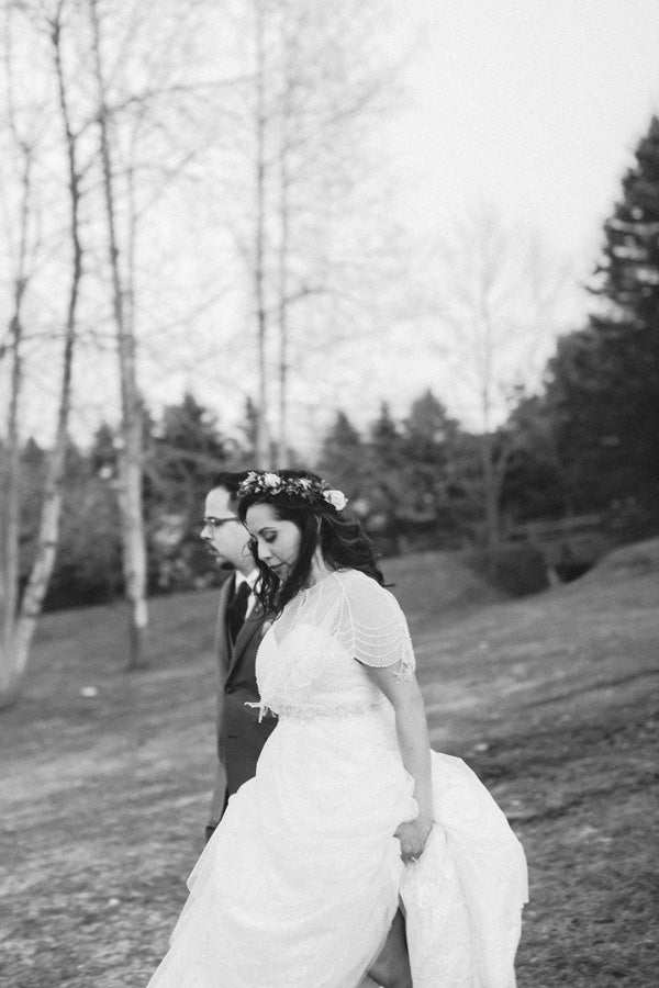 bride and groom walking through the woods black and white