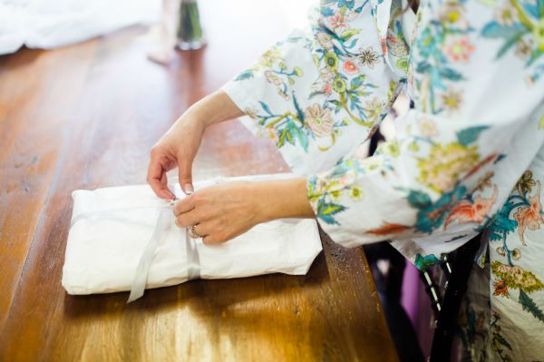 bride getting ready in kimono style robe unwrapping veil from The Mantilla Company