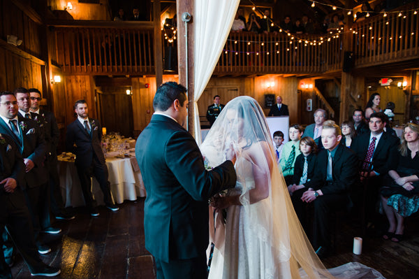 bride in cathedral length mantilla company veil lifting blusher