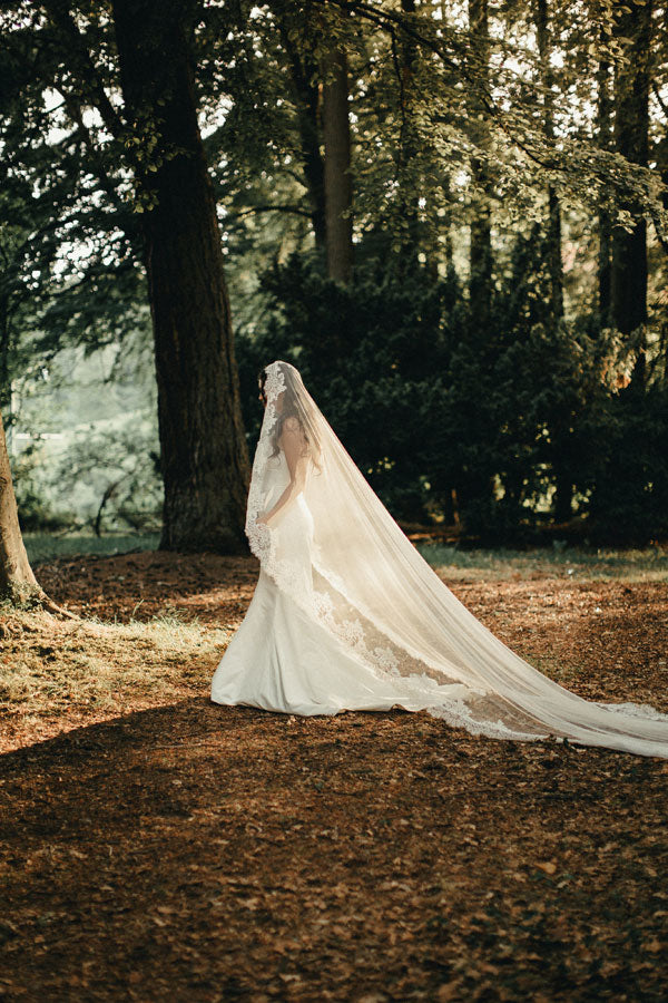 bride walking through the forest with long lace veil