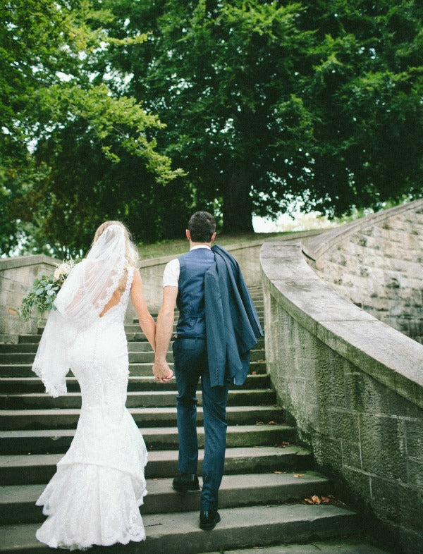 Mantilla Veil bride and groom holding hands walking up stairs