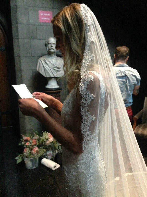 bride reading vows in mantilla veil