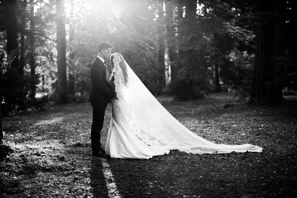 portrait of bride and groom in the forest with long veil