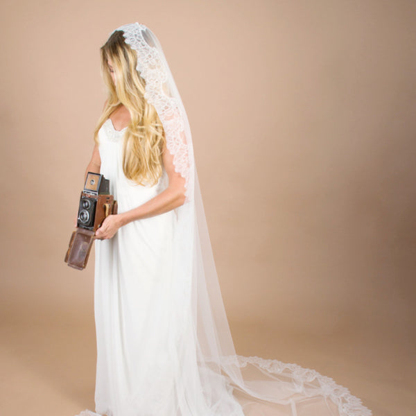bride with vintage camera in mantilla veil