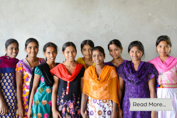 Nine Indian women standing together wearing bright colored saris and smiling