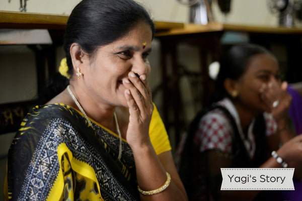 Indian woman wearing black yellow sari and laughing with hand covering her mouth