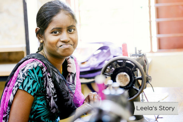 Young Indian woman wearing teal and black sari sitting at sewing machine