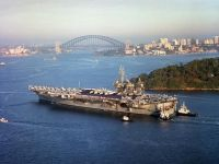 A port side view showing US Navy (USN) Sailors manning the rails of the USS CONSTELLATION (CV 64), as the ship isassisted by tugboats, while entering the harbor at Sydney Australia, during Operation SOUTHERN WATCH.<br>- 2001