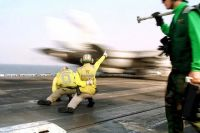 Two US Navy (USN) Catapult and Arresting Gear Officers, launch a USN F/A-18C Hornet aircraft from the flight deck of the USN KITTY HAWK CLASS: Aircraft Carrier, USS CONSTELLATION (CV 64), while conducting flight operations while underway in the Arabian Sea, supporting Operation SOUTHERN WATCH.<br>- 1999
