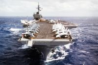 A bow view of the aircraft carrier USS CONSTELLATION (CV-64) underway. Various aircraft of the carrier's air wing are parked on the flight deck.<br>-1988