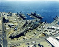 An aerial view of Hunter's Point Naval Shipyard with three docked aircraft carriers