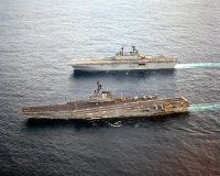 The aircraft carrier USS CORAL SEA (CV 43), foreground, and the amphibious assault ship USS WASP (LHD 1) sail alongside one another. The CORAL SEA is returning to Norfolk, Virginia, at the end of its last deployment.