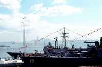Pennants and bunting decorate the guided missile frigate USS FLATLEY (FFG-21) and the guided missile cruiser USS DALE (CG-19), docked at the pier during the station's opening day ceremonies. Aircraft fly in formation overhead in honor of the event, 06/25/1990