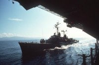 A port bow view of the destroyer USS FORREST SHERMAN (DD-931) alongside an aircraft carrier during an underway replenishment. <br>June 1974