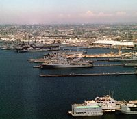 Aerial view of the Naval Station. Some of the ships docked are the dock landing ship USS MONTICELLO (LSD 35), the guided missile cruiser USS FOX (CG 33), and the tank landing ships USS TUSCALOOSA (LST 1189), USS BRISTOL COUNTY (LST 1198), USS FRESNO (LST 1182), and the amphibious assault ship USS BELLEAU WOOD (LHA 3). - 1984 San Diego, CA