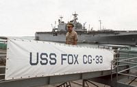 Commander (CDR) Joe Betancourt, executive officer of the guided missile cruiser USS FOX (CG 33), crosses the ship's brow. The amphibious assault ship USS TARAWA (LHA 1) is in the background. - 1986