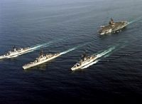 An aerial port bow view of various U.S. Navy ships of the aircraft carrier KITTY HAWK battle group underway. They are, left to right, frigate USS STEIN (FF-1065), guided missile cruiser USS HALSEY (CG-23), frigate USS BARBEY (FF-1088) and the aircraft carrier USS KITTY HAWK (CV-63), background. - 1987