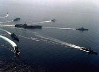 An aerial starboard view of the aircraft carrier USS KITTY HAWK (CV-63) underway during maneuvers with its battle group. The ships are, clockwise from top left: guided missile frigate USS VANDEGRIFT (FFG-48), combat stores ship USS MARS (AFS-1), frigate USS BARBEY (FF-1088), guided missile cruiser USS HALSEY (CG-23), guided missile frigate USS STEIN (FF-1065), guided missile destroyer USS CALLAGHAN (DDG-994), ammunition ship USS MOUNT HOOD (AE-29) and the KITTY HAWK, center. - 1987