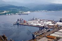 An aerial view of the harbor with docked ships, including the guided missile frigate USS BROOKE (FFG-1) and the guided missile cruiser USS HALSEY (CG-23) docked bow to bow with the Filipino corvette RPS RIZAL (PS-69) and the combat stores ship USS SAN JOSE (AFS-7) docked at the stern of the destroyer USS O'BRIEN (DD-975) and the guided missile destroyer USS BUCHANAN (DDG-14). - 1981 Subic Bay, PI