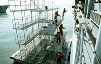 Several sailors stand on a floating scaffold as they paint the side of the guided missile cruiser USS HARRY E. YARNELL (CG-17), 04/01/1991