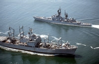 The amphibious cargo ship USS EL PASO (LKA 117), foreground, passes the guided missile cruiser USS YARNELL (CG 17), 05/01/1990