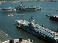 A tug boat accompanies the aircraft carrier USS FORRESTAL (CV-59) as the ship departs the city at the end of Fleet Week. In the foreground is the decommissioned anti-submarine warfare aircraft carrier INTREPID (CVS-11), which is operated as a museum.<br>1989